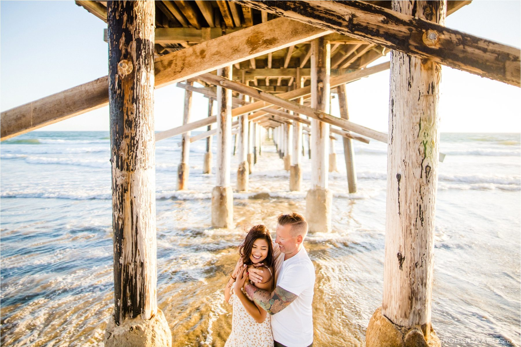 A Newport Beach, Orange County engagement photography session under the pier by the destination wedding photographer Robert Paetz.